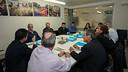 diverses persones assegudes al voltant d'una taula en una sala de reunions