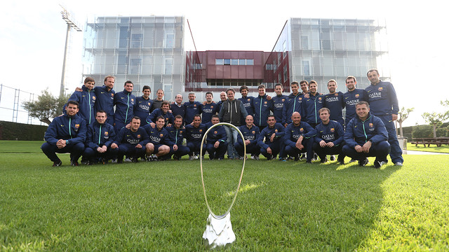 The FC Barcelona youth coaches pose with the trophy on the garden outside La Masia