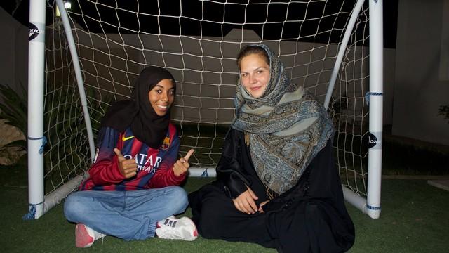 Dues noies somrient amb vel al cap, assegudes sota una porteria de futbol.