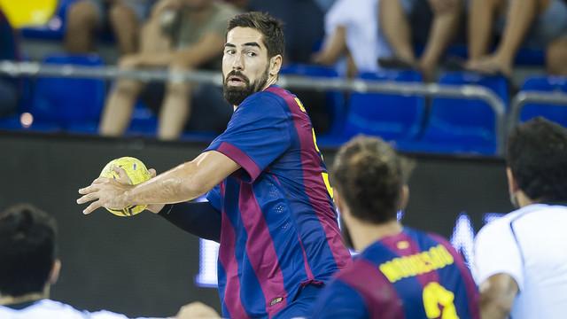 Karabatic intenta jugar la pilota davant l'oposició de la defensa