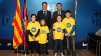 Un grup de nens amb unes samarretes on s'hi llegeix la paraula 'Barçakids' amb Bartomeu i Bertolín