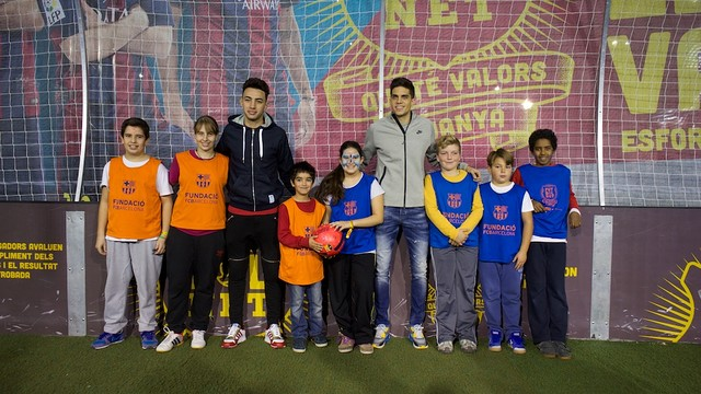 Bartra i Munir es fan una foto amb un grup de nens en un minicamp de futbol