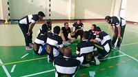 Asseguts al terra en cercle, un grup d'homes parlen entre ells. Porten una samarreta de FutbolNet.