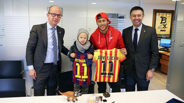 Neymar dan anaknya memperlihatkan kartu keanggotaan FCB