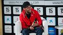 Neymar, sentado em um sofá sorrindo e com um microfone na mão.