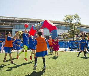 Un grup de nens juguen a 'FutbolNet' sobre un camp de gespa artificial a l'esplana del Camp Nou